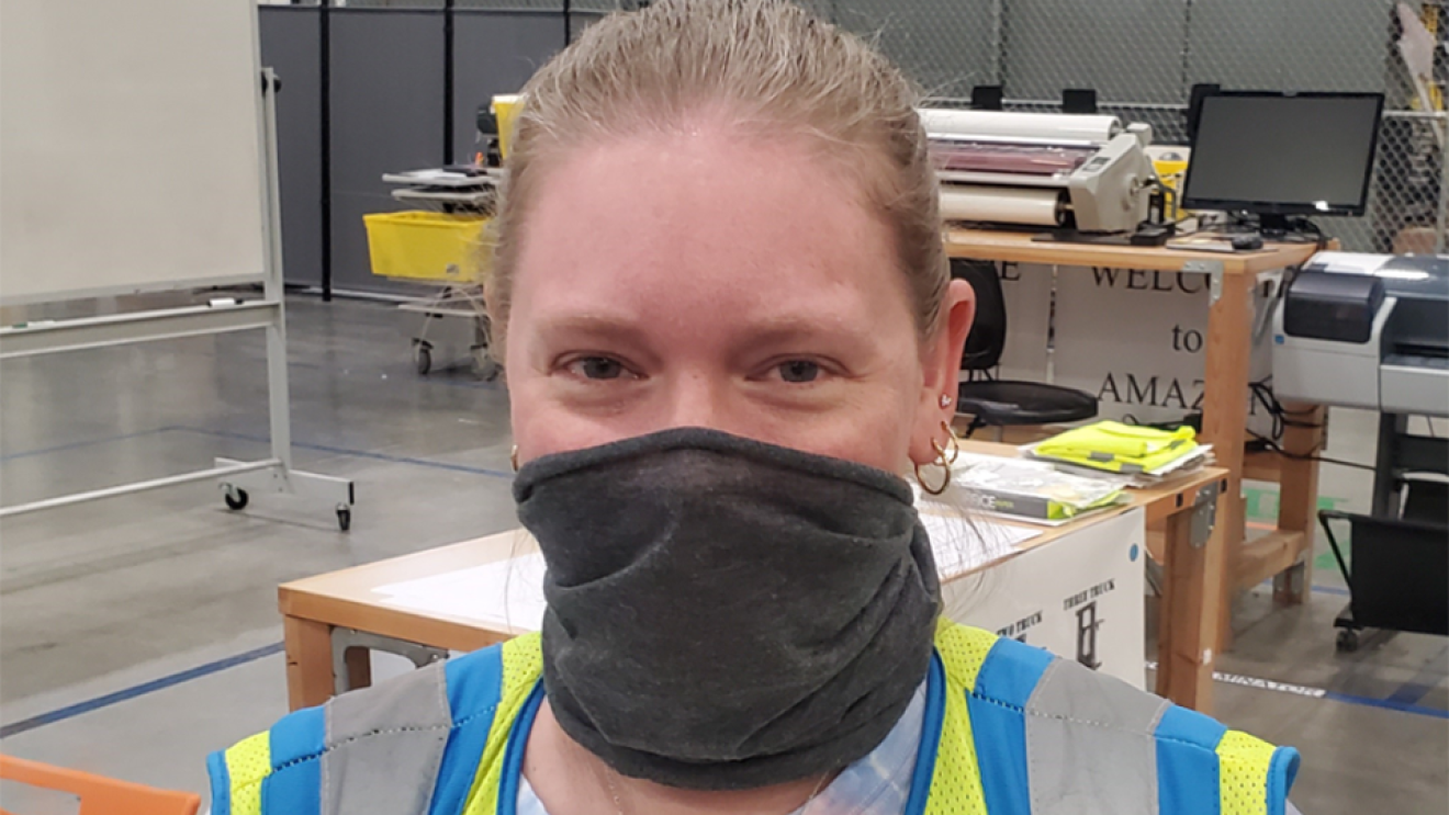 A woman wears a face mask and safety vest. On her vest, a green, crocheted heart pin is attached.