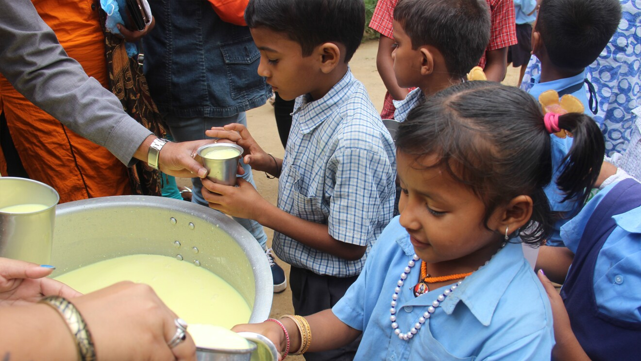 A school girl from a government school getting his glass of milk, even as the boy behind him in the queue looks on