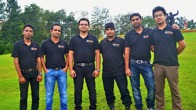 The team that makes up Arcatron stands outside and smiles for the camera. The team is six men and they are wearing Arcatron polo shirts.
