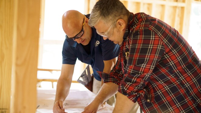 Two men wearing safety glasses are leaning over a construction project blueprint, wood framing is seen in the foreground and background. One man is wearing a shirt with Pro.com embroidered on it.
