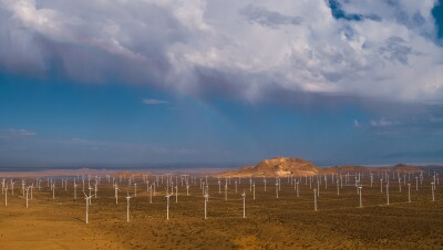 An aerial view of wind farm in a mountainous desert landscape.