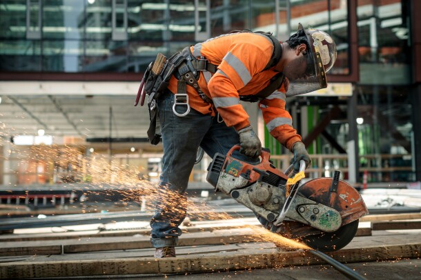A man in a construction helmet and orange safety jacket is photographed at a construction site on Amazon's campus in Seattle, WA. He is using a circular saw to cut through metal.