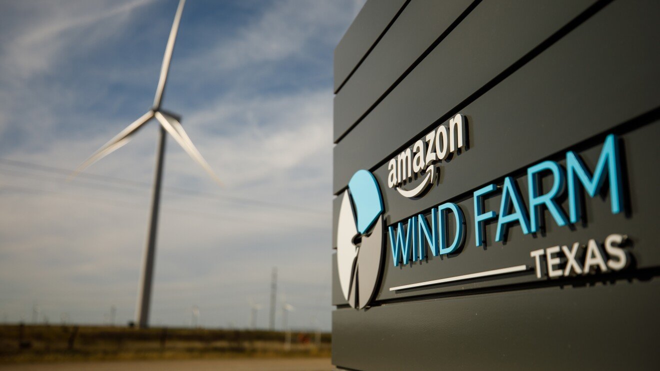 View of the sign entering the Amazon Wind Farm in Texas with a wind turbine in the background.