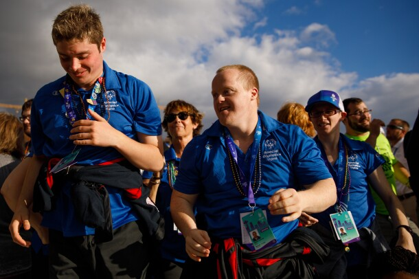 "Special Olympics athletes and attendees from Virginia appear to lead a group of others. Two smiling males are in the foreground, seeming to be moving forward. In the middle ground, two other individuals wearing ""Special Olympics Virginia"" shirts are facing the same direction. In the background, more attendees are seen."