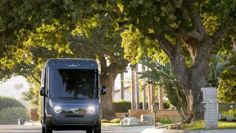 An Amazon-branded Rivian vehicle drives through the streets in Southern California.