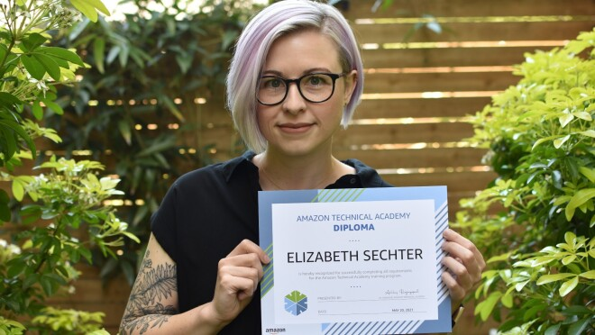Elizabeth Sechter holds up her ATA diploma while she poses in front of greenery outside. She has short blonde hair with light purple highlights. She wears black-framed eye glasses, a black short-sleeved shirt and has a tattoo on her right elbow.