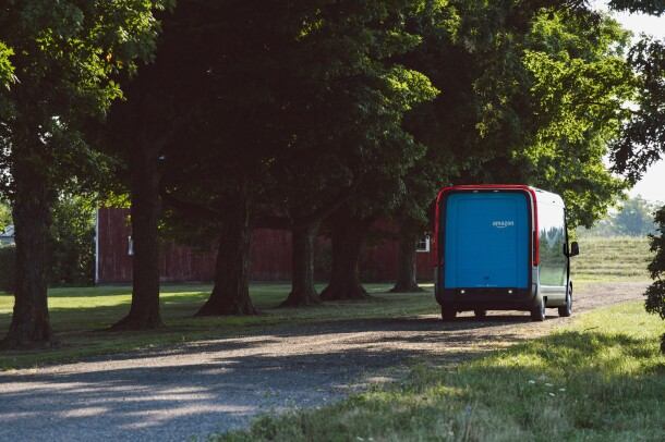 An electric delivery vehicle seen from behind, driving along a wooded road.