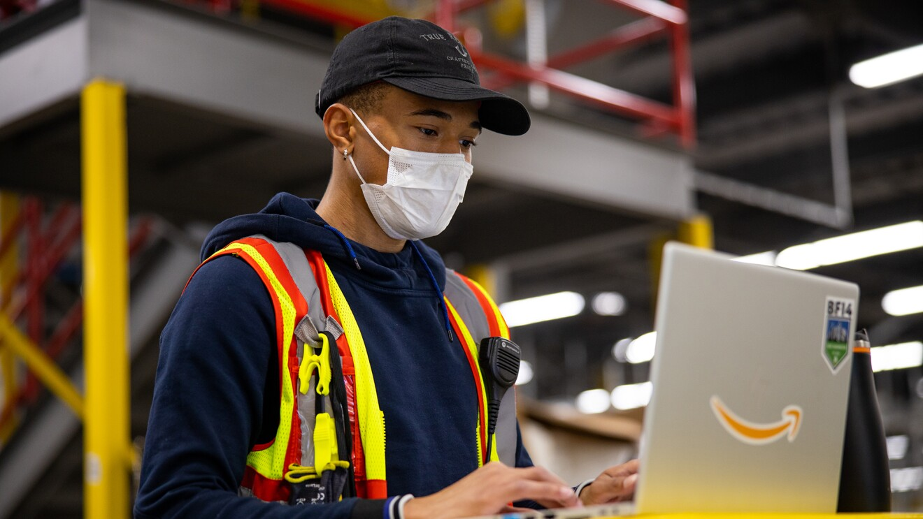 A man is wearing a mask while working on a laptop in one of Amazon's fulfillment centers.