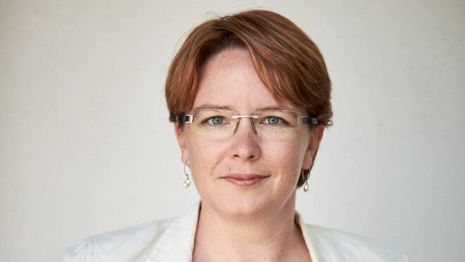 A woman smiles for a headshot photo in front of a white background while wearing a white blazer and glasses.