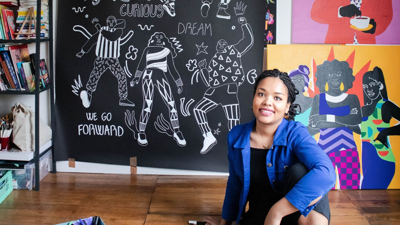 a Black woman, Aurelia Durand, sits on the wooden floor of her studio. Her artwork is displayed on the wall behind her, with saturated colors, and stylized people.