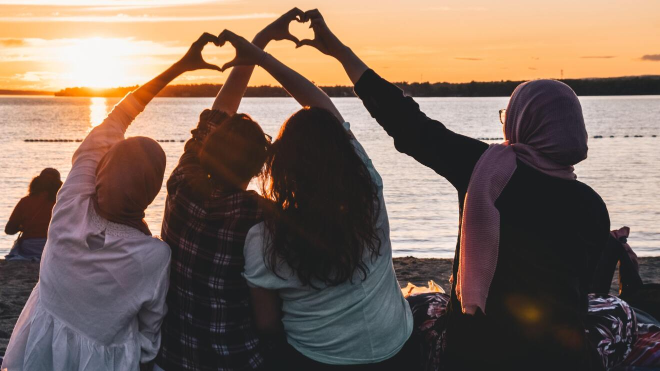 Girls sitting on a beach front their hands in heart shape