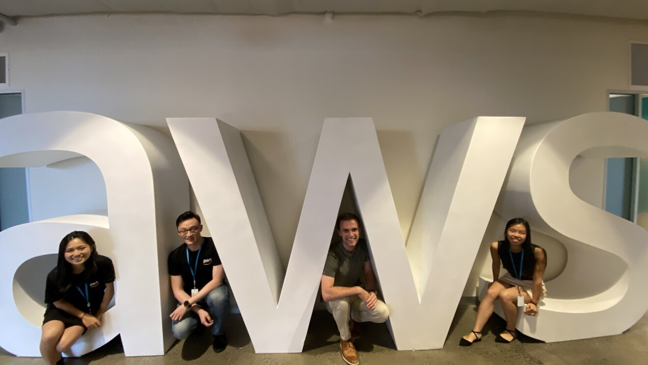 Four Amazon interns crouch to pose amid the AWS logo in white, against a white background.