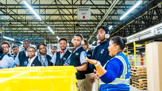 Students attend a tour of an Amazon robotics fulfillment center