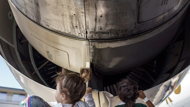 Two young children peek inside the body of a Prime Air aircraft.