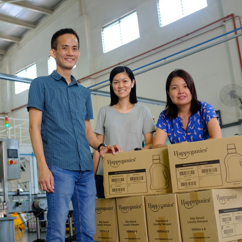 The team behind Happyganics, with their products in a factory