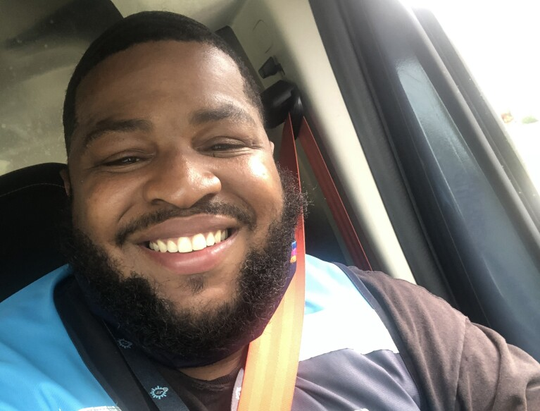 An image of a man smiling for a selfie in his car. He is wearing the blue Amazon delivery vest.
