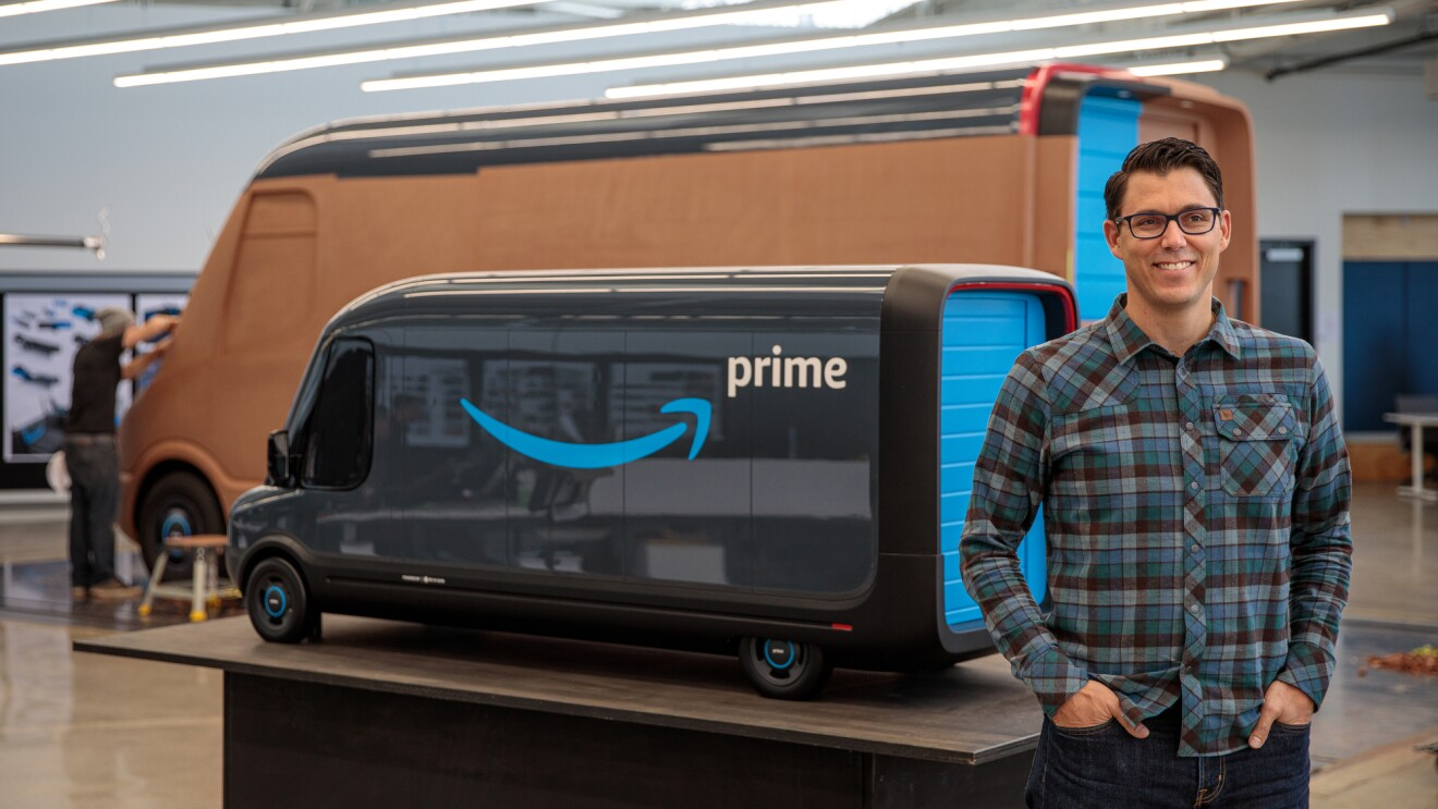 A man in a plaid shirt stands in front of a scale model of an Amazon delivery vehicle and a full-size clay model of the vehicle.