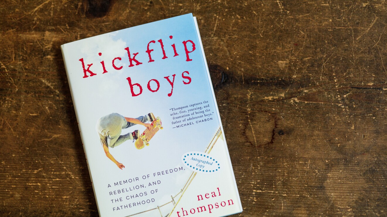 A book sits on a table. The cover shows an image of a skateboarder flying through the air at a skate bowl. The title of the book is Kickflip Boys.
