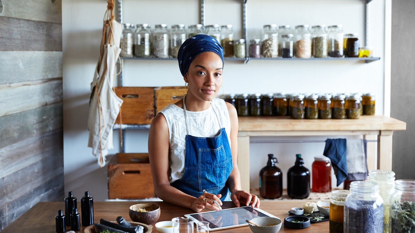 A woman stands at a table, working on an iPad. Behind her are jars of preserves or other homemade products, and there are herbs and ingredients in front of her.