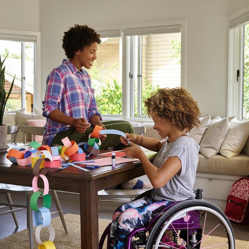 ダイニングテーブルに座った母親が、娘と一緒に紙の輪を作りながら笑っています。背後のテーブルに置かれているのはAmazon Echoです。