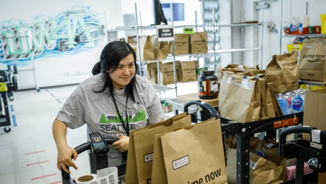 Erika Lopez pushes a cart through the Prime Now facility in Seattle, Washington. On her cart, there are brown paper shopping bags with the Prime Now logo. More bags are on shiny metal shelves in the background.