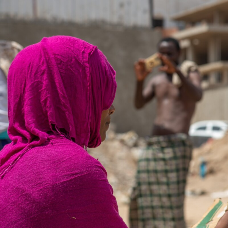 A migrant woman wears a bright pink head scarf, looking away from the camera while sitting in a large open space. Fellow migrant men are also around her in the area.