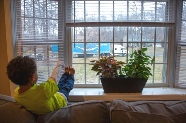 A boy sits on the back of a couch and looks out a window. Outside, on the far side of a lawn, there is a semi truck with the Amazon smile logo.