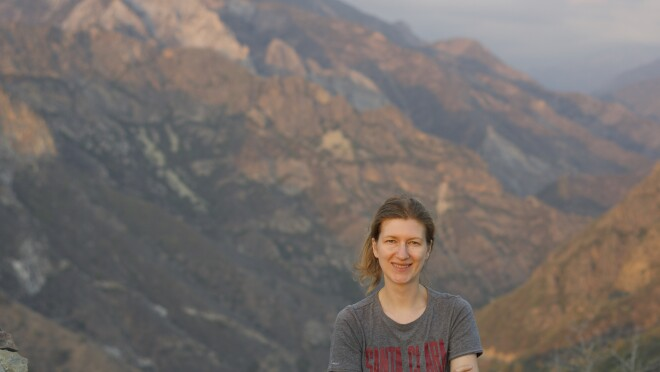 A woman smiles for a photo while standing on a trail with mountains in the background behind her. She is wearing a Santa Clara University t-shirt.