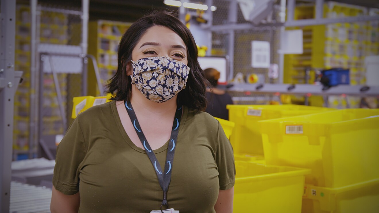 A woman wearing a t-shirt, lanyard, and face mask stands in an Amazon fulfillment center.