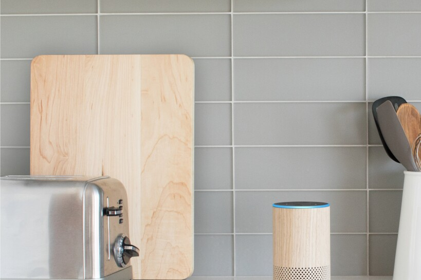 An Oak colored Amazon Echo on a modern-styled kitchen counter.