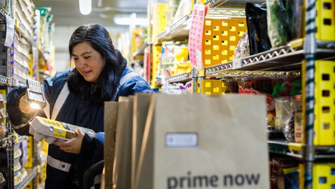 Prime Now associate Erika Lopez scans a carton of eggs. In the foreground, there are two brown shopping bags with the Prime Now logo.