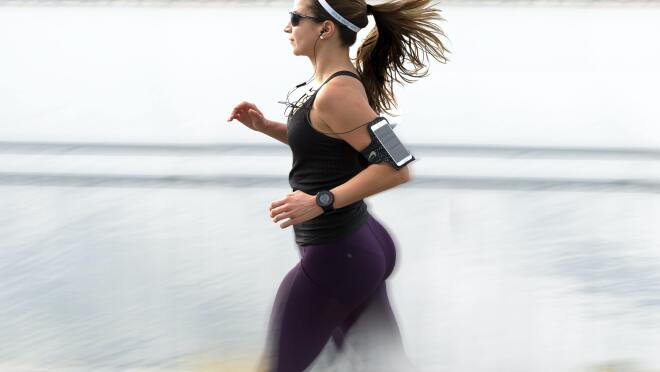 A girl running with an activity tracker strapped to her hand