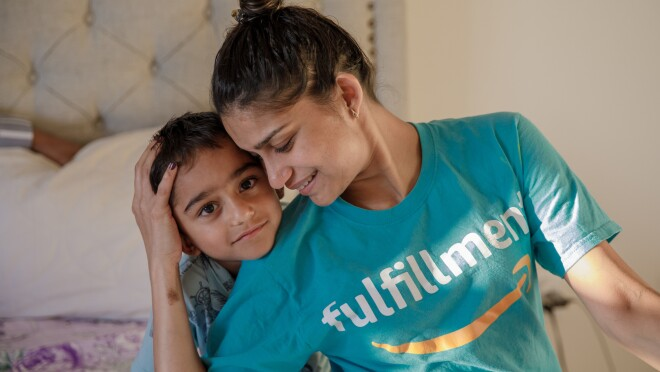 """A young boy leans on the shoulder of a woman who cradles the side of his head with one hand. The woman has her hair up and wears a T-shirt with the Amazon smile logo and the word """"fulfillment."""""""