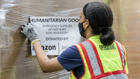 A woman wearing a mask navigates a pallet of humanitarian goods in an Amazon fulfillment center