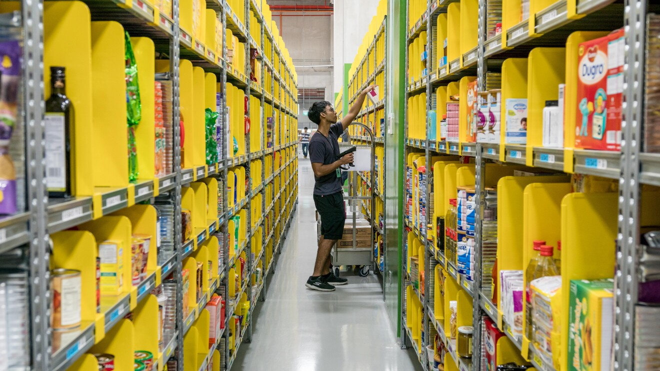 An Amazon Fulfillment Center employee stands in an aisle of yellow containers picking product for a customer's order.