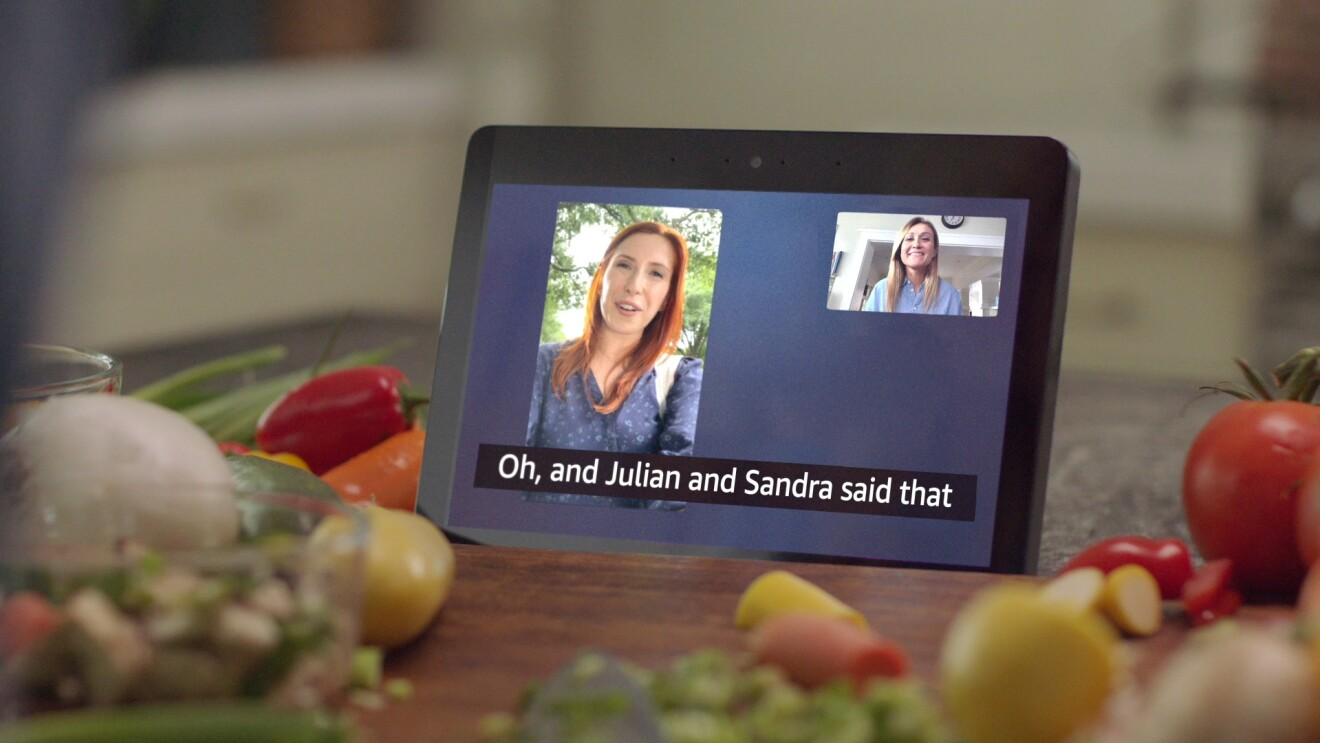 A video call featuring two women on an Amazon Echo Show 8 with call captioning sits atop a kitchen counter surrounded by vegetables.