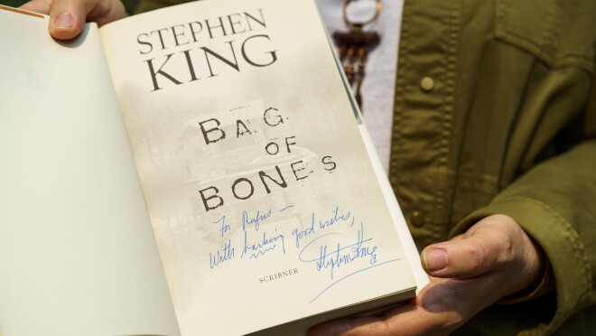 """A man holds the book Bag of Bones by Stephen King. The inscription reads 'For Rufus, with barking good wishes."""""""