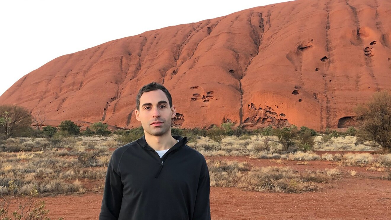 A man wearing a half-zip jacket and t-shirt stands in an arid location near the brush