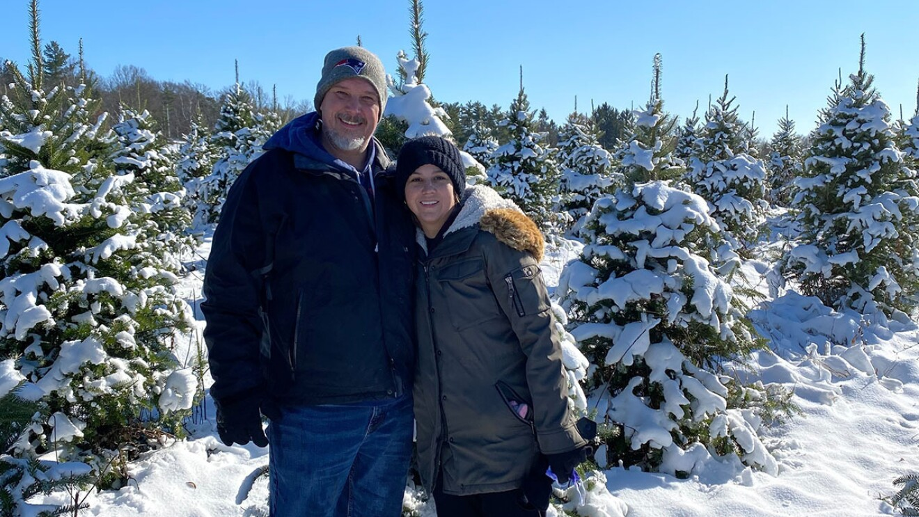 A woman and man stand together, wearing winter jackets among snow-covered coniferous trees.