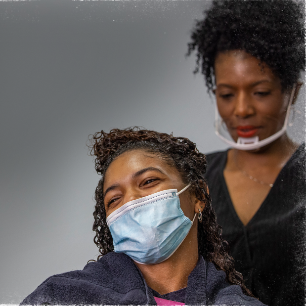 A woman wears a face mask in a stylist chair in a salon. Behind her, another woman wearing a mask is styling the first woman's hair.