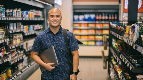 A man holding a laptop computer in one arm smiles at the camera from within an Amazon Fresh grocery store.