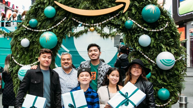 An image of a family smiling for a photo in front of a wreath. The kids are holding presents with white wrapping and green bows.