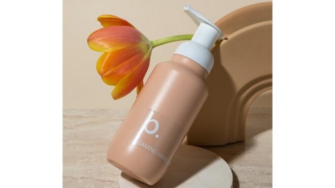A bottle of baresop foaming hand soap. A orange tulip is next to the bottle.