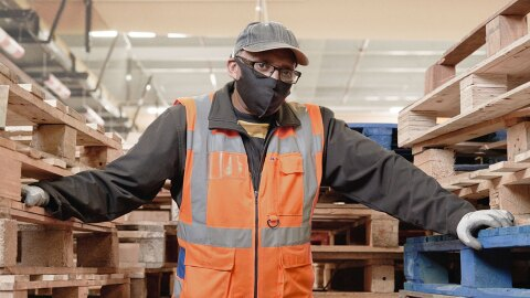 Amazon associate Melvyn wears a mask, high visibility vest, and safety gloves while standing amongst stacks of pallets on an Amazon fulfillment center shipping dock