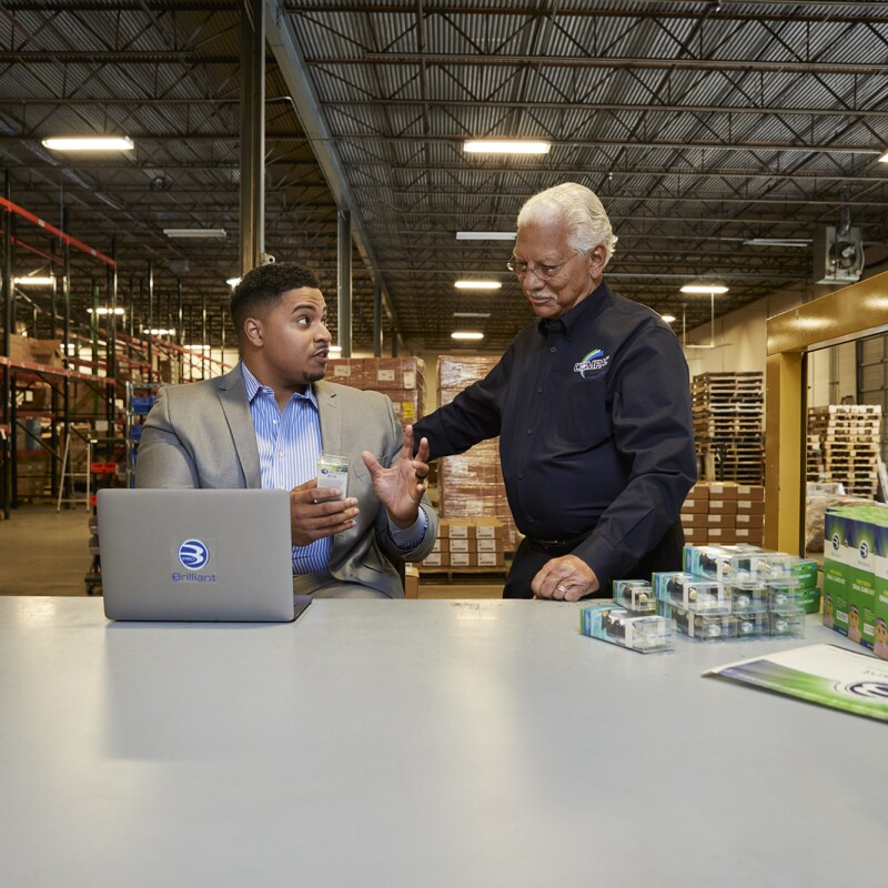 Two men speak to one another at a tabletop surface in a warehouse facility