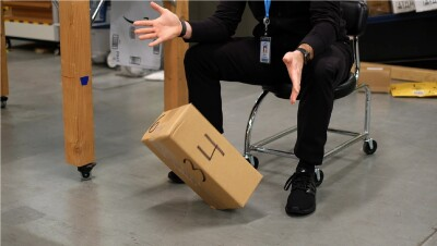 A person drops a package on the ground during a testing simulation.