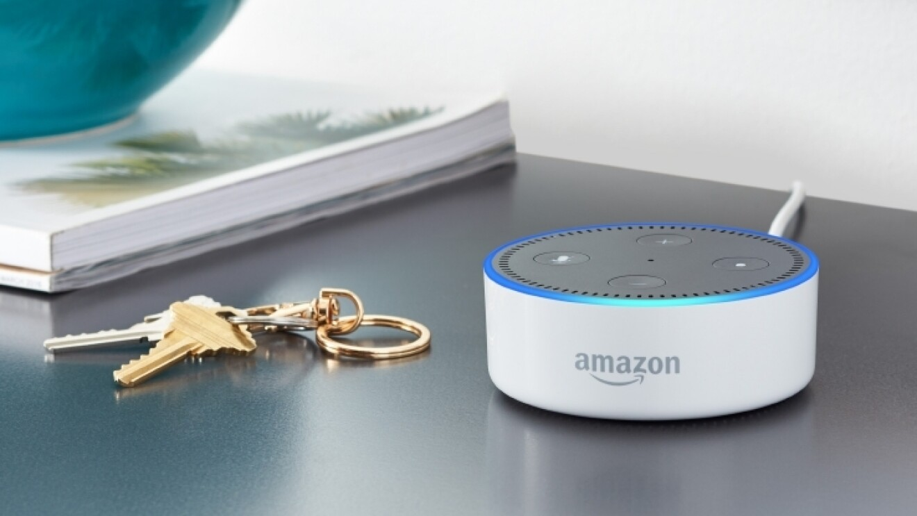 A white Amazon Echo Dot on a night stand, next to a pair of keys.