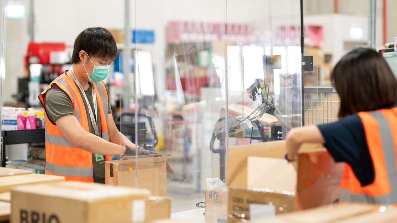 Operations team at the fulfilment center in Amazon Singapore packing orders
