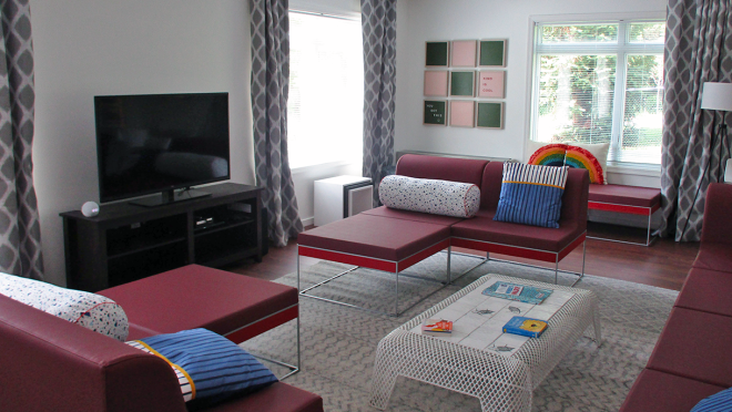 The living room at the Ronald McDonald House in Washington D.C. features a room filled with couches and fun throw pillows. There is a white coffee table with games on top and an Amazon Echo Dot sits next to a TV.