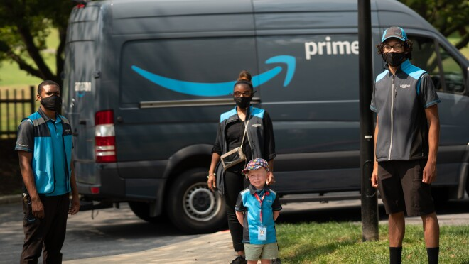 An image of a boy standing in front of an Amazon van while wearing an Amazon employee vest. There are two employees standing for the photo with him.
